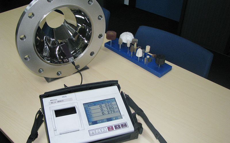 Measuring the Ra value of a composite part using a roughness tester or Ra meter.